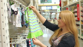 La mujer joven elige la ropa para el niño en tienda almacen de metraje de vídeo
