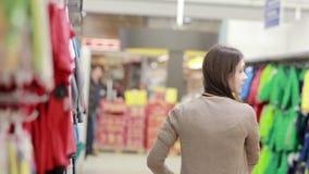 La mujer joven elige la ropa para un niño almacen de metraje de vídeo