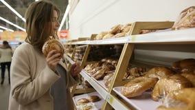 La mujer joven elige la torta en el supermercado almacen de metraje de vídeo