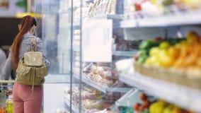 La mujer joven elige las frutas en el supermercado almacen de video
