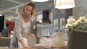 La mujer joven elige platos en el supermercado almacen de metraje de vídeo