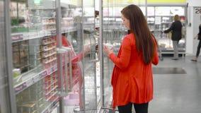 La mujer joven elige la producción de lechería en la tienda metrajes