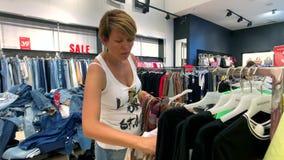 La mujer joven elige la ropa en la tienda de la ropa almacen de video