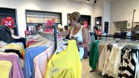 La mujer joven elige la ropa en la tienda de la ropa almacen de metraje de vídeo