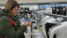 La mujer joven elige un mezclador en un supermercado de los aparatos electrodomésticos almacen de metraje de vídeo