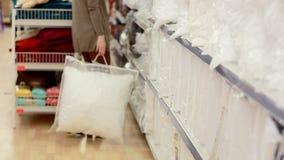 La mujer joven eligió una almohada en un supermercado metrajes