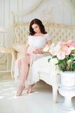 La mujer joven embarazada de la morenita se sienta en cama cerca del florero con las rosas y mira el vientre Imagen de archivo