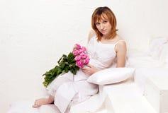 La mujer joven embarazada en una alineada blanca con la unión de rosas imágenes de archivo libres de regalías