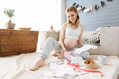 La mujer joven embarazada que sonríe feliz en el nuevo bebé viste Imagenes de archivo
