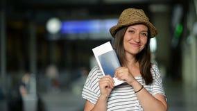 La mujer joven emocionada con el boleto y el pasaporte en sus manos está esperando un aeroplano en el aeropuerto Marcador borroso almacen de video