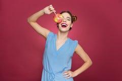 La mujer joven emocionada feliz cubrió su ojo con la piruleta colorida Fotos de archivo