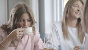 La mujer joven emocional cuenta a sus amigos la historia, gesticulando activamente metrajes