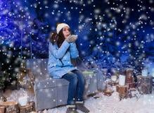La mujer joven en abajo chaqueta azul sopla los copos de nieve mientras que sienta o Fotografía de archivo libre de regalías