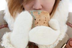 La mujer joven en abrigo de invierno y las manoplas mullidas blancas detiene al alfarero Imagen de archivo libre de regalías