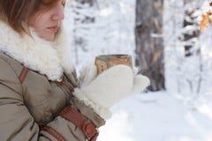 La mujer joven en abrigo de invierno y las manoplas mullidas blancas detiene al alfarero Foto de archivo libre de regalías