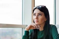 La mujer joven en la anticipación mira hacia fuera la ventana enorme a la calle foto de archivo libre de regalías