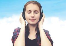 La mujer joven en auriculares se relaja y escucha la música Imagen de archivo
