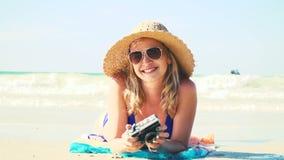 La mujer joven en bikini azul está mintiendo en la playa con una cámara del vintage y tiene un sombrero del sol encendido almacen de metraje de vídeo