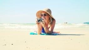 La mujer joven en bikini azul está mintiendo en la playa con una cámara del vintage y tiene un sombrero del sol encendido almacen de video