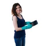 La mujer joven en camiseta oscura y los guantes de goma verdes sobre blanco aislaron el fondo Foto de archivo