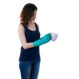 La mujer joven en camiseta oscura y los guantes de goma verdes sobre blanco aislaron el fondo Fotografía de archivo