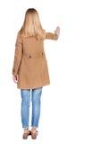 La mujer joven en capa aprieta en algo Imagen de archivo libre de regalías