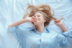 La mujer joven en casa que ponía en cama despertó el pelo ensuciado de la visión superior Imagen de archivo