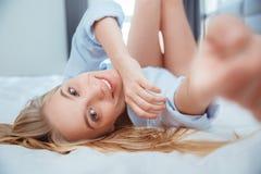La mujer joven en casa que ponía en cama despertó el primer conmovedor de la cámara Imagen de archivo