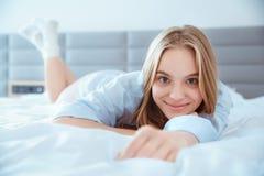 La mujer joven en casa que ponía en cama despertó el primer juguetón Fotografía de archivo