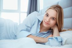 La mujer joven en casa que ponía en cama despertó fresco Imagenes de archivo
