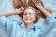 La mujer joven en casa que ponía en cama despertó las manos de la visión superior encima de juguetón Fotografía de archivo