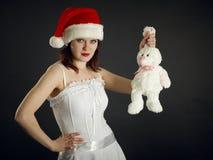 La mujer joven en casquillo de la Navidad sostiene un conejo Imagen de archivo libre de regalías