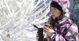 La mujer joven en chaqueta caliente se calienta con café caliente en parque del invierno almacen de metraje de vídeo