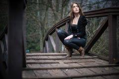 La mujer joven en chaqueta se agacha en el puente Foto de archivo