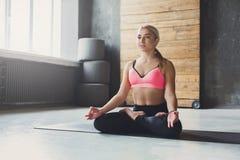 La mujer joven en clase de la yoga, relaja actitud de la meditación Fotos de archivo