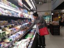 La mujer joven en la compra de la bebida y de la comida de la leche, en el supermercado del eón, noche imagen de archivo