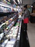 La mujer joven en la compra de la bebida y de la comida de la leche, en el supermercado del eón, noche foto de archivo libre de regalías