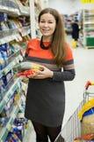 La mujer joven en controles del colmado dos paquetes de pastas en las manos, soportes acerca a la carretilla de las compras imágenes de archivo libres de regalías