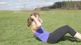 La mujer joven en deportes adapta hacer sentar-UPS al aire libre
