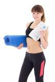 La mujer joven en deportes lleva con la botella de agua y de estera aisladas Imágenes de archivo libres de regalías