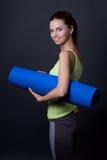 La mujer joven en deportes lleva la presentación con la estera de la yoga sobre gris Fotos de archivo libres de regalías