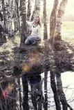La mujer joven en el banco del lago del bosque, Fotos de archivo