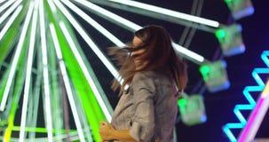 La mujer joven en el carnaval se coloca de mirada para arriba en temor metrajes