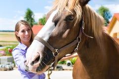 La mujer joven en el establo con el caballo y es feliz Fotografía de archivo libre de regalías