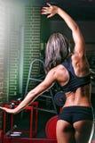 La mujer joven en el gimnasio con ella de nuevo a la cámara hace un ejercicio Foto de archivo