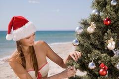 La mujer joven en el sombrero de Papá Noel en la playa adorna bolas de un árbol de navidad Imagenes de archivo