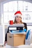 La mujer joven en el sombrero de santa desanimaba en oficina Fotos de archivo