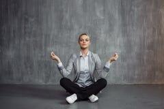 La mujer joven en el traje de negocios que se sienta en la actitud de Lotus, energía del restablecimiento, medita Salud y trabajo foto de archivo