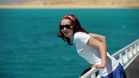 La mujer joven en gafas de sol camina en el barco del yate almacen de metraje de vídeo