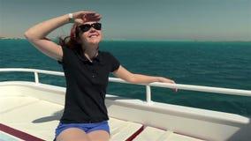 La mujer joven en gafas de sol se sienta en el barco del yate almacen de metraje de vídeo